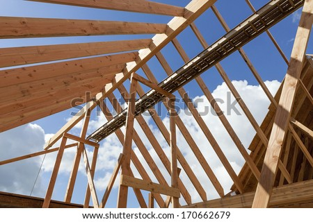 Horizontal shot of post and beam roof construction with view of sky/New Home construction with exposed beams and blue sky background