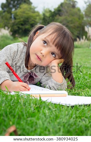 Horizontal shot of 4 year old girl drawing with color pencil and looking away.
