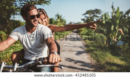 Horizontal shot of young couple riding motorbike. Man riding on a motorcycle with girlfriend pointing away on rural road. - stock photo