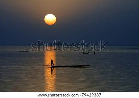 Horizontal silhouette of fishing canoes at sunset on Niger River in Mali - stock photo