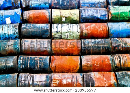 Horizontal staple of colorful used oil drums on a storage site - stock photo