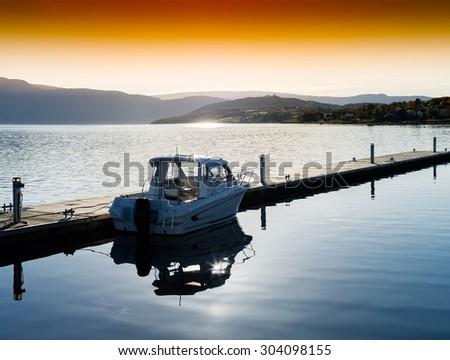 Horizontal sunset Norway boat near pier landscape background - stock photo