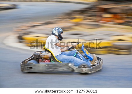 Horizontal take of an Asian driver and go kart as they zoom past on a public race track in Goa India - stock photo