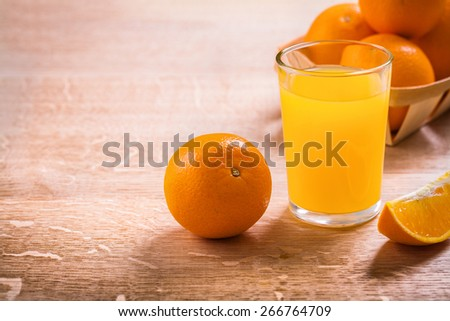 horizontal version glass with juice and oranges on wooden board with organized copyspace  - stock photo