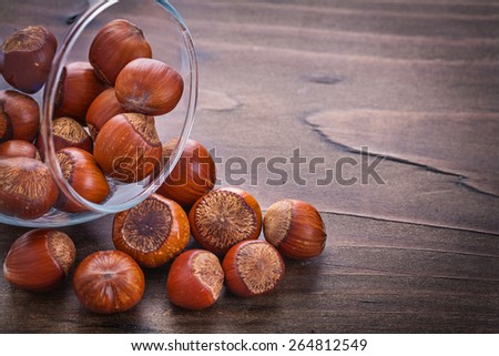 horizontal version stack of hazelnuts in glass bowl on vintage wooden board food and drink still life  - stock photo