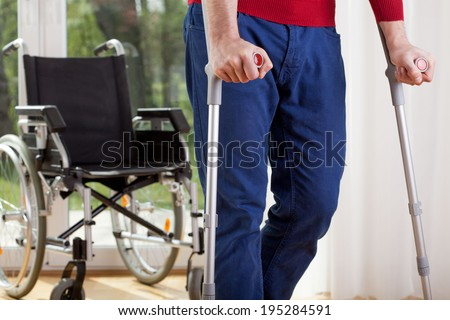 Horizontal view of a disabled man on crutches - stock photo