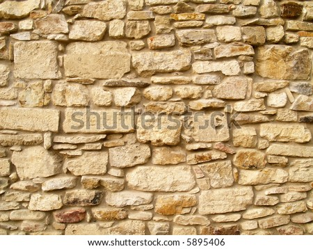 Horizontal view of a layered, sandstone exterior wall building facade. A close up of a brick wall which can be used as background - stock photo