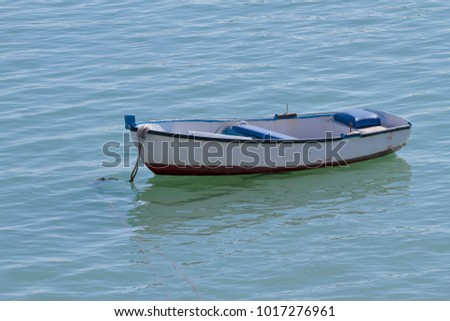horizontal view of a small wooden boat anchored in the sea