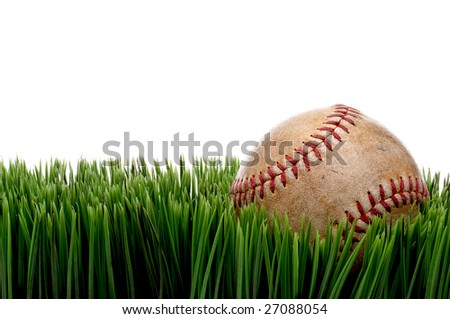 Horizontal view of an old worn sports baseball on grass against a white background - stock photo
