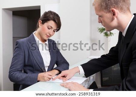Horizontal view of attractive businesswoman signing document - stock photo