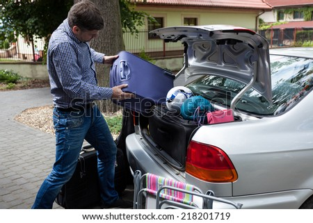 Horizontal view of car trunk full of luggage - stock photo