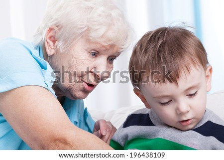 Horizontal view of glad grandma with little boy - stock photo