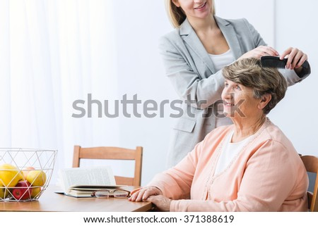 Horizontal view of granddaughter combing grandma's hair - stock photo