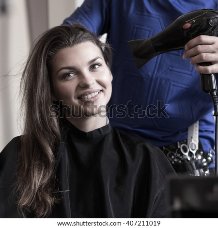 Horizontal view of hairstylist drying woman's hair - stock photo