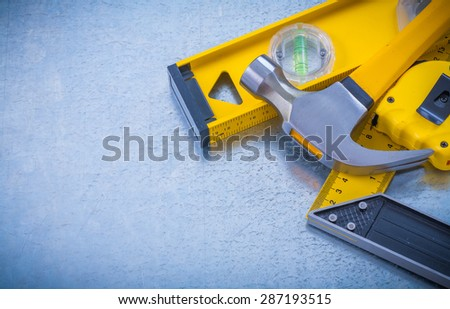 Horizontal view of hammer measuring tape construction level square ruler on industrial metallic background maintenance concept. - stock photo