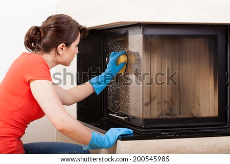 Horizontal view of housekeeper cleaning the fireplace - stock photo