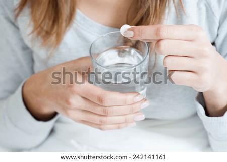 Horizontal view of ill woman taking aspirin - stock photo