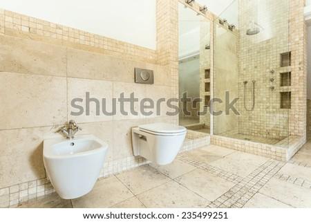 Horizontal view of interior of beige bathroom - stock photo