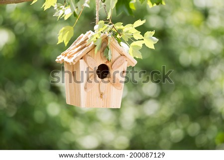 Horizontal view of new wooden birdhouse hanging on tree branch outdoors with blurred out green trees in background during summer day - stock photo
