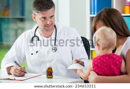 Horizontal view of pediatrician giving prescription - stock photo