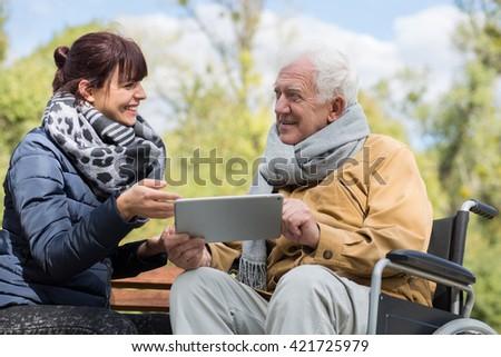 Horizontal view of senior man using tablet - stock photo