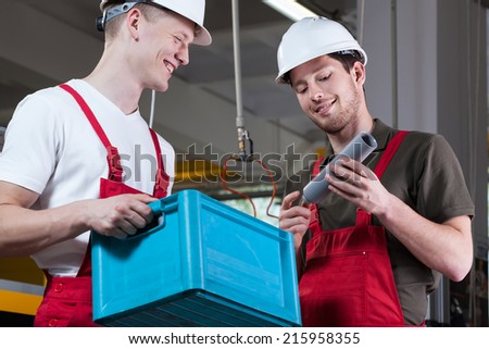 Horizontal view of two smiling factory workers - stock photo