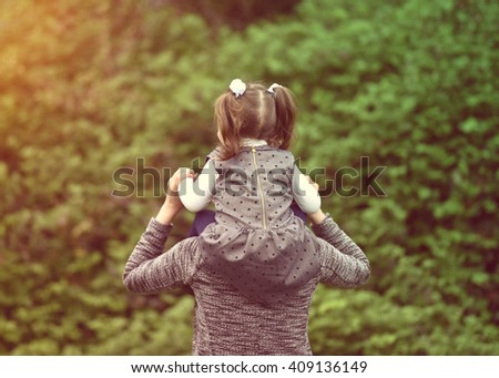 horizontal vintage portrait of a young girl sitting on her mother's shoulders and walking in the park on a sunny day in spring with their backs turned wearing a gray dress, white blouse, gray jacket - stock photo