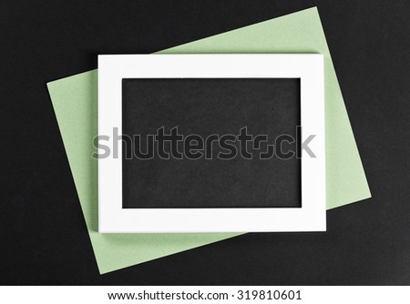 horizontal white photo frame with black field and green paper under angle on black background isolated with real shadows - stock photo