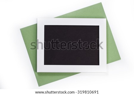horizontal white photo frame with black field and green paper under angle on white background isolated with real shadows - stock photo