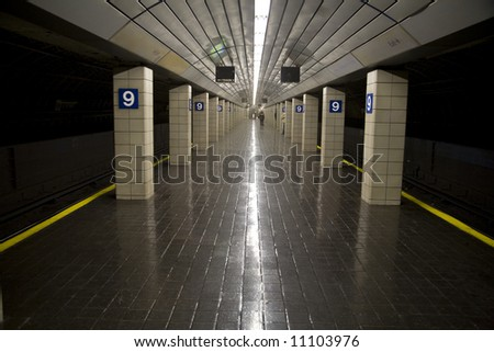 Horizontal wide angle image of a sparsely filled subway station - stock photo