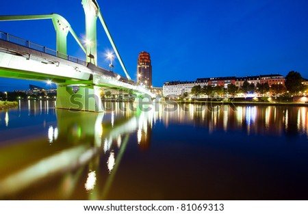 Horizontal wide angle perspective of the green bridge reflecting in the river - stock photo