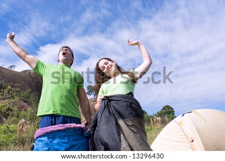 Horizontally framed outdoor shot, looking up towards the sky, of a young attractive couple standing in their sleeping bags yawning as they awake from their slumber. - stock photo
