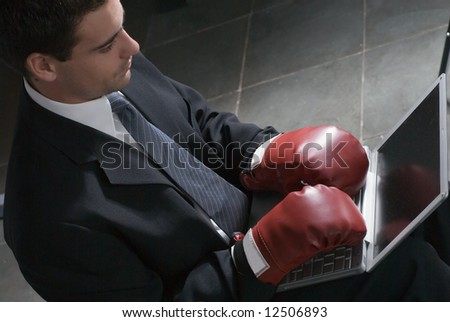 Horizontally framed shot of a young, attractive businessman trying to type on his laptop while wearing boxing gloves - stock photo
