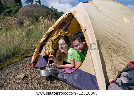 Horizontally framed shot of an attractive young couple cooking a meal in their tent. Shot is framed against a beautiful blue sky - stock photo
