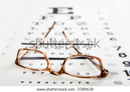 horn rim eyeglasses sittin on top of an eye exam chart, forground sharp and background soft - stock photo