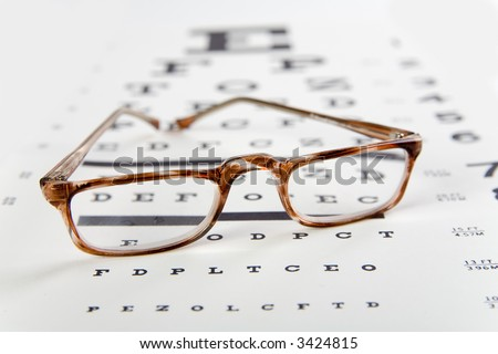 horn rim readingglasses sitting on top of an eye exam chart, foreground sharp and background soft - stock photo