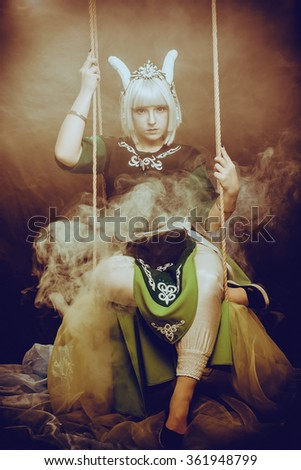 Horned girl sitting on a swing - stock photo