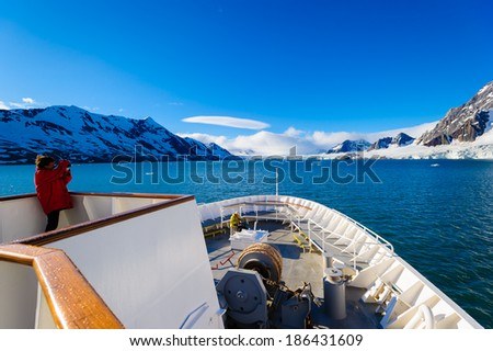 HORNSUND, SVALBARD, NORWAY - JULY 26,  2010:  Photographer on the National Geographic Explorer cruise ship in the Arctic.