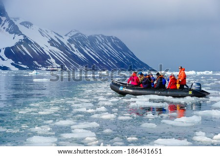 HORNSUND, SVALBARD,NORWAY - JULY 26, 2010: Tourists from the National Geographic Explorer cruise ship on inflatable rafts in the Artic Ocean exploring a fijord in the Arctic. - stock photo