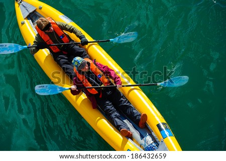 HORNSUND, SVALBARD,NORWAY - JULY 26,  2010: Tourists from the National Geographic Explorer cruise ship on inflatable kayaks in the Artic Ocean exploring a fijord in the Arctic. - stock photo