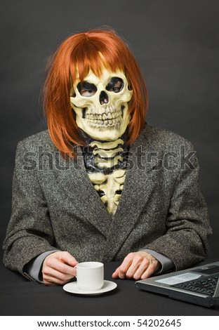 Horrible man - a skeleton with red hair drinking coffee on dark background - stock photo