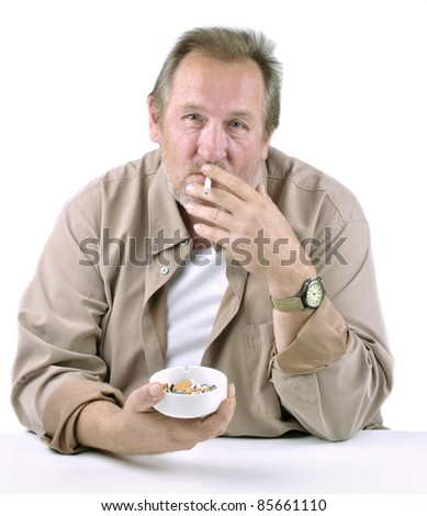 horrified man in his 50s sitting at a table with a cigarette and ashtray - stock photo