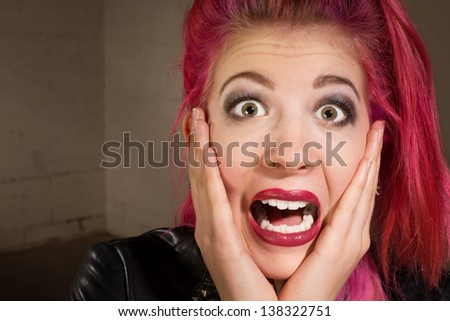 Horrified young punk rocker female in pink hair - stock photo