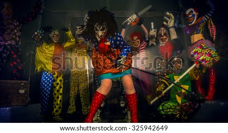 Horror clown party. The clown stands with the scythe of death. - stock photo