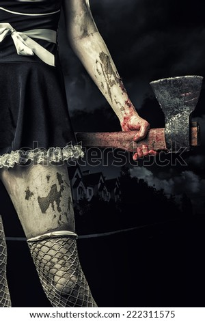 Horror. Dirty woman's hand holding a bloody ax outdoor in night town - stock photo