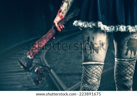 Horror. Dirty woman's hand holding a bloody axe outdoor in night forest - stock photo