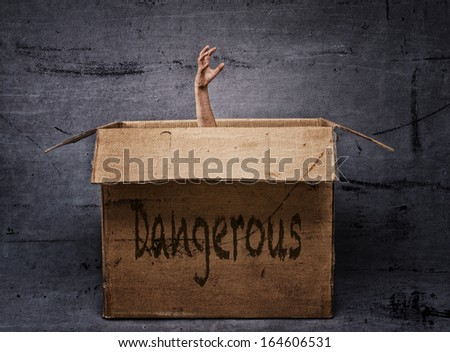 Horror hand rising out of box in dark and dirty environment - stock photo