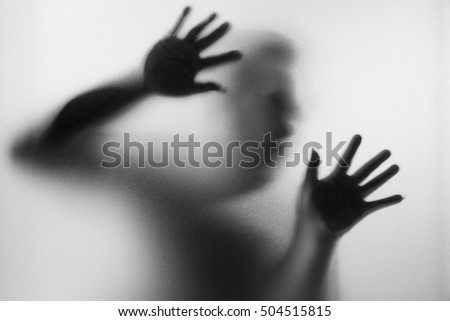 Horror man behind the matte glass in black and white. Blurry hand and body figure abstraction.Halloween background.Black and white picture