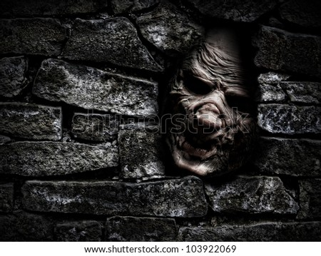 Horror monster looking out from hole in the wall - stock photo