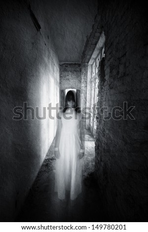 Horror movie scene with a girl dressed in white in a desolated house - stock photo